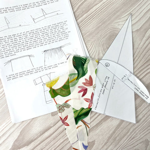 Close up image of instruction booklet an a piece of fabric with green and pink