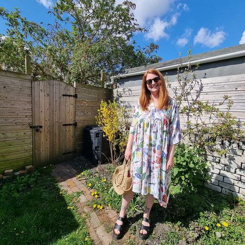 Image of Debbie, a white woman, standing in a garden in a multicoloured dress.