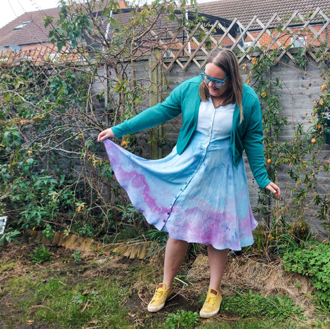 Image of Laura, a white woman wearing am ice dye border dress with green cardigan and yellow trainers