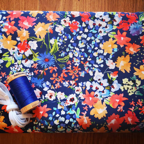 Image of floral fabric on a blue background with a spool of blue thread
