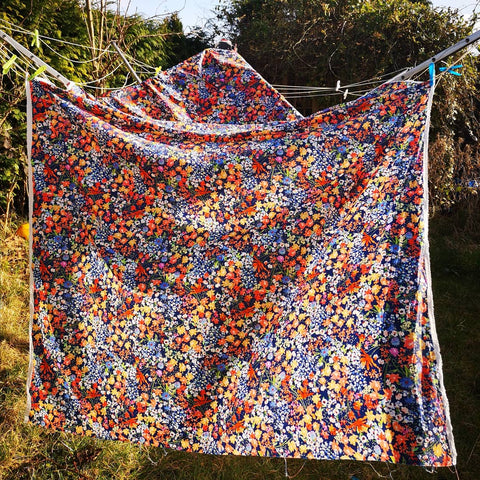 Image of floral fabric on a blue background hanging on a washing line