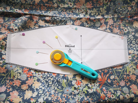 Image of pattern piece on the floral fabric with a rotary cutter