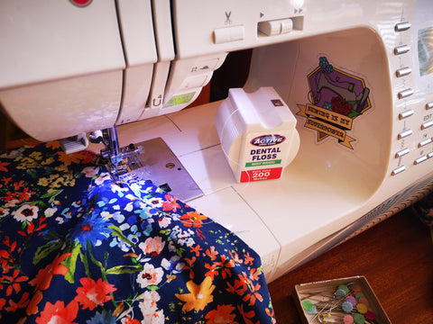Image of floral fabric  with a blue background and a sewing machine