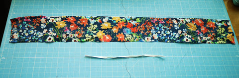 Image of a long piece of floral fabric with elastic for a scrunchie