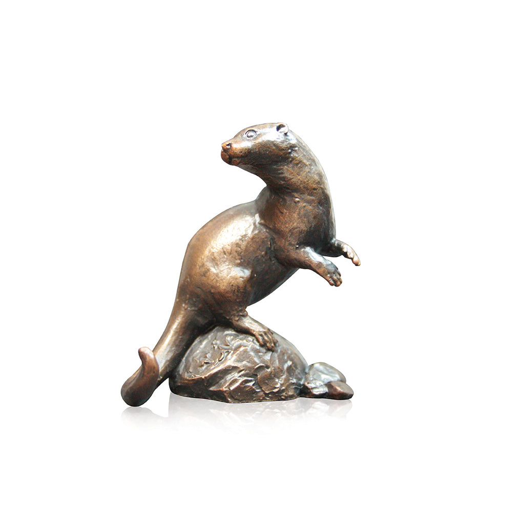 river otter sitting on rock bronze sculpture