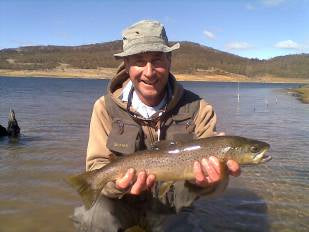 man trout flyfishing snowy mountains