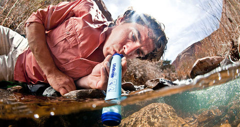 lifestraw man drinking from river