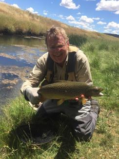 Murray catching a large fish on the fly