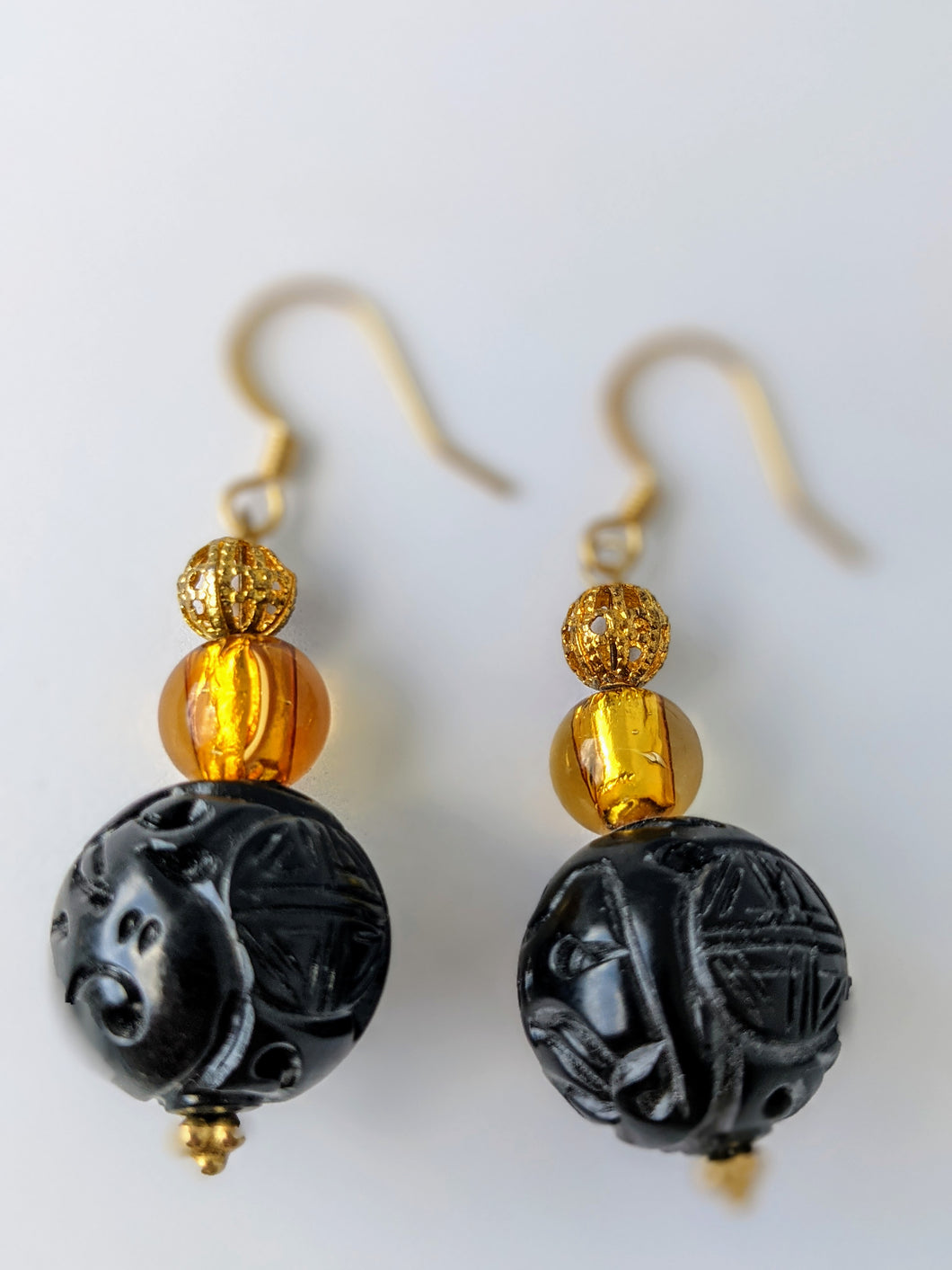Carved Plastic Black Bead and Gold Murano Glass Earrings