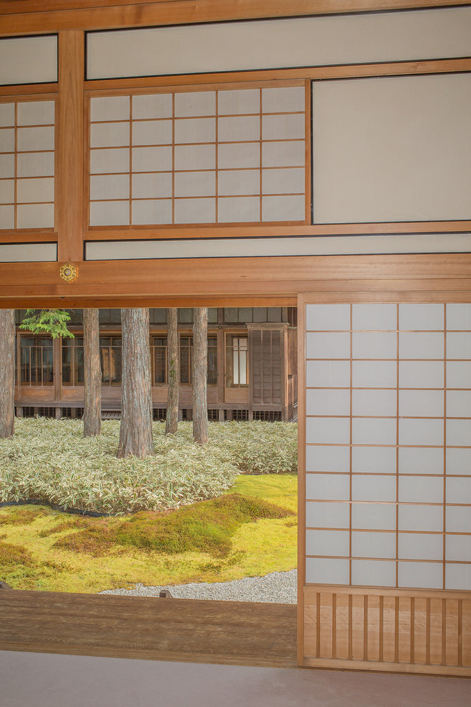 Inside a building with traditional Japanese architecture and a view to the outdoor garden