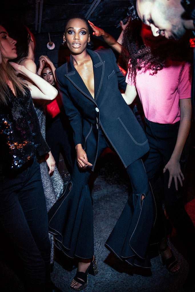 Woman in suit partying at night