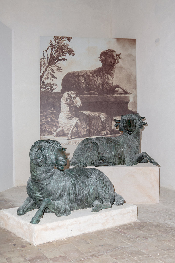 Two sheep sculptures in front of a painting of two sheep