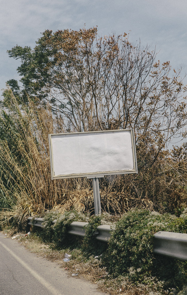 Blank white sign on the side of a road