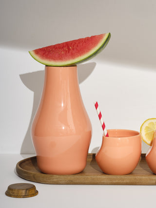 One coral carafe with a watermelon slice balanced on top next to one coral medium cup with a straw on a medium tray