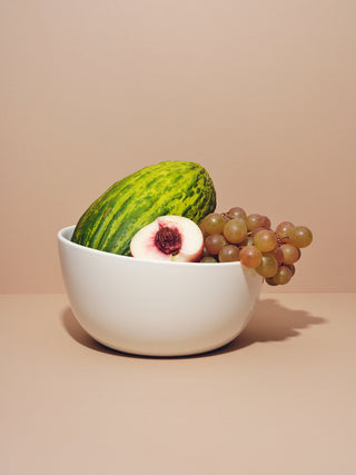 Deep serving bowl filled with watermelon, grapes and halved peaches