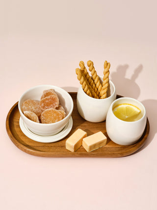 Two white small cups and a switch bowl with snacks on a small wooden tray