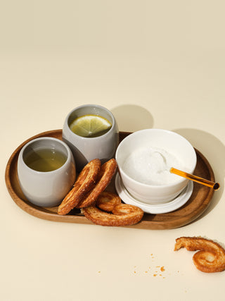 Two grey small cups with lemon tea next to a switch bowl with sugar on a small wooden tray