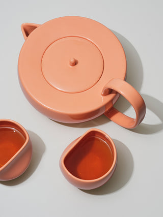 Large coral teapot next to two asymmetrical coral medium cups