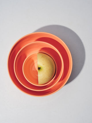Set of nesting coral bowls with half an apple in center