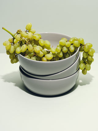 Stack of grey bowls with grapes arching over