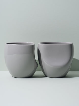 Two grey assymmetrical cups lined next to each other
