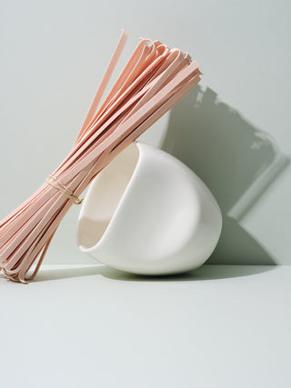 White asymmetrical cup tilted against dried pasta