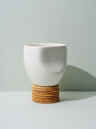 White ceramic cup with recessed side on stack on crackers