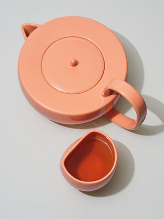 Large coral teapot next to asymmetrical cup