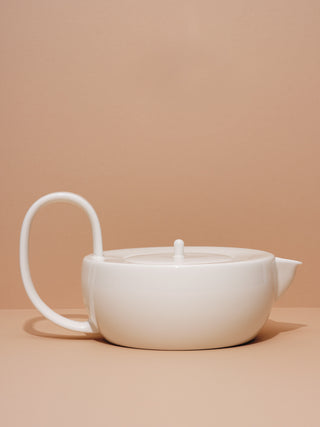 White ceramic teapot with large looping handle on its side