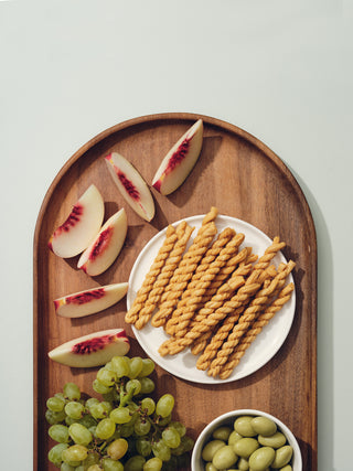 Oval wooden tray filled with peach slices, bread twists, olives, and grapes