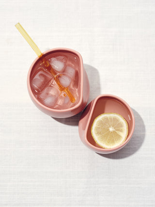 Top view of two mauve asymetical ceramic cups full of water, one with ice and a straw and one with lemon.