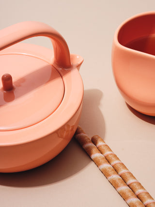 Small coral teapot and cup with biscuits
