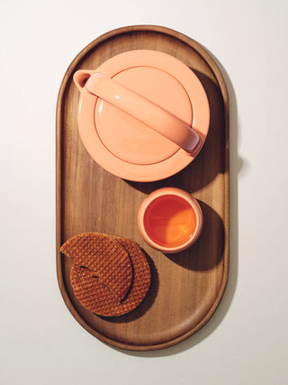 A small teapot, cup, and waffle treat on top of oval wooden tray