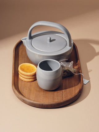 Small grey teapot with a small grey cup next to biscuits and a teabag on top of a medium tray