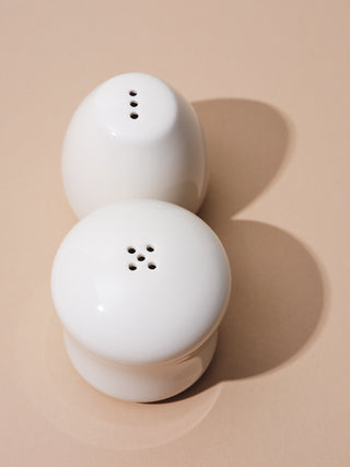 White salt and pepper shakers on beige background