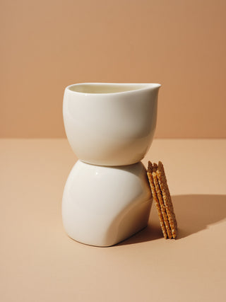 A white cup and creamer stacked with biscuits tilted on them