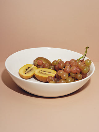 Serving bowl holding red grapes and halved kiwis