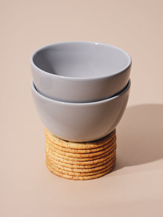 Two small gray bowls on top of a stack of crackers