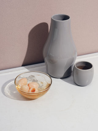 A grey carafe, small ceramic cup, and glass bowl with small pale pink fruits on a white table.