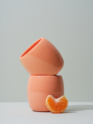 Coral ceramic cups stacked with a tangerine piece