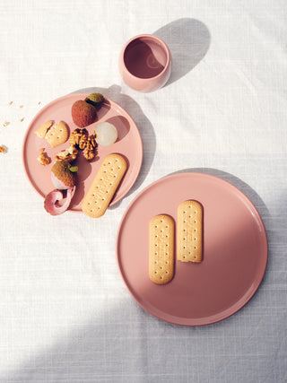 Rose colored small and medium sized plate with biscuits and lychees