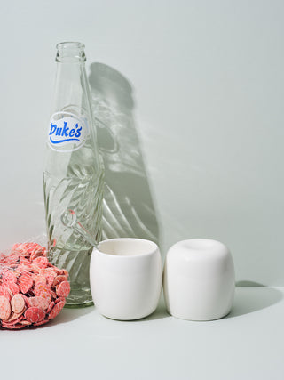 Short white ceramic cups next to empty vintage soda bottle and pink pumpkin seeds