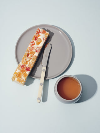 Grey ceramic plate with a slice of fruit bread, knife, and small matching cup beside