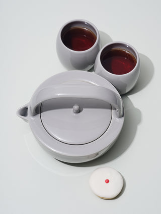 Grey ceramic teapot next to two short grey cups and a cupcake