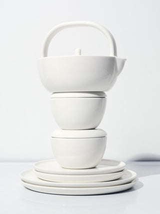 White ceramic plates, bowls, and teapot sculpturally stacked.
