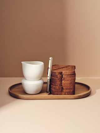 Stack of white ceramic and bread on oval wooden tray