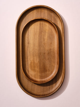 A small wooden tray on top of a medium wooden tray