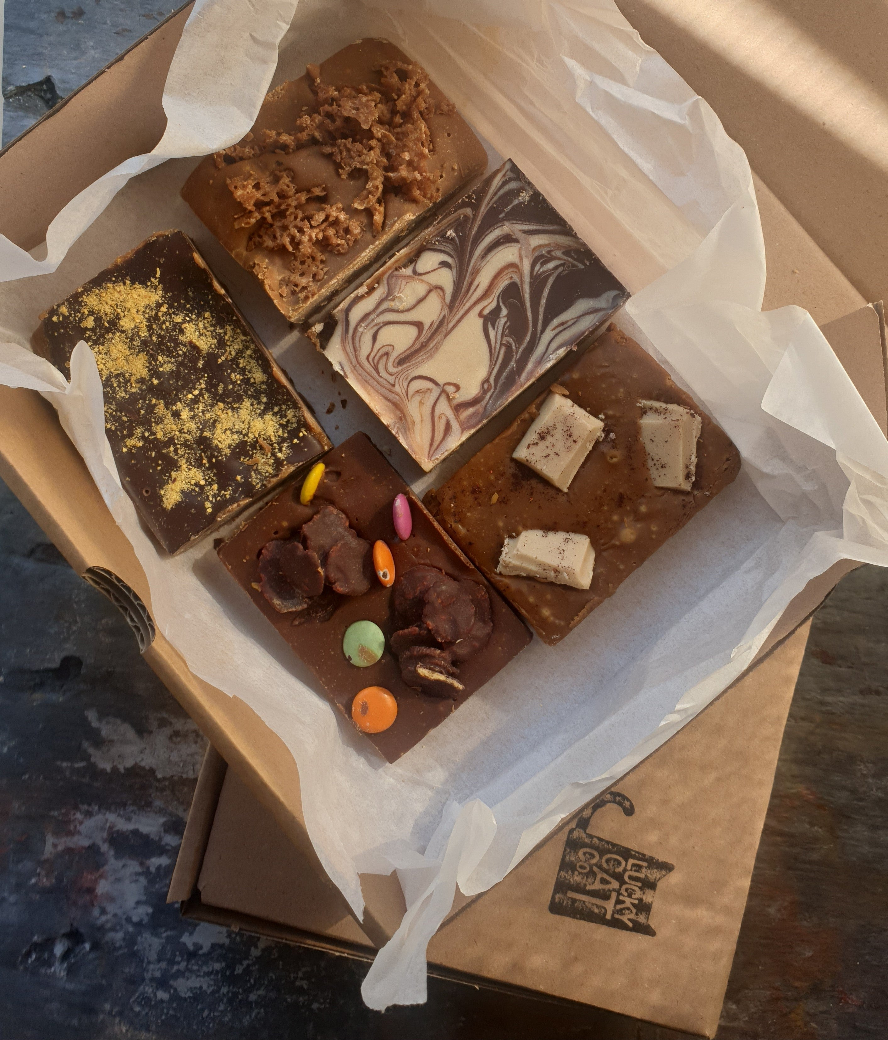 An open box containing 5 different slabs. They include 1 xginger fudge, 1 x millionaires slice, 1 x vanilla & white choc, 1 x smarties fudge & 1 x choc orange fudge