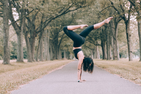 woman practicing handstand in the park