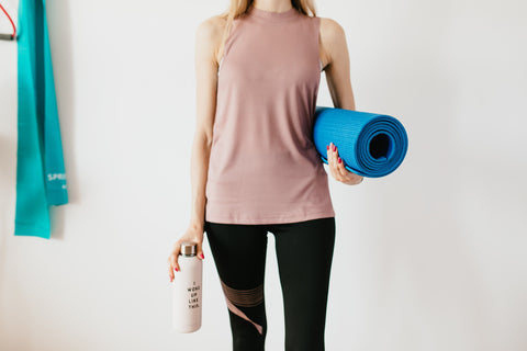 woman holding water bottle and yoga mat